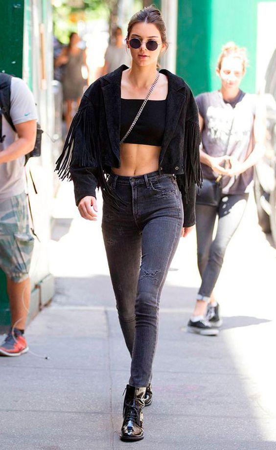 10 Looks para quem ama franjas. Kendall Jenner, jaqueta preta de camurça com franjas, boho, top cropped preto, barriga de fora, calça preta skinny, coturno preto