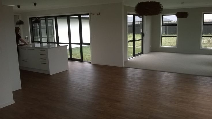 """Open plan living. Looking spacious prior to furniture coming in. """"Vintage Timber 3046"""" vinyl planking was used in the kitchen, dining, family room, and entry."""