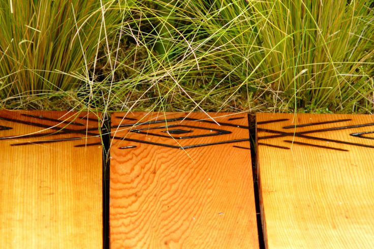 Designed by Carolyn Grohmann. Stipa tenuissima and scorched pattern on cedar boardwalk.