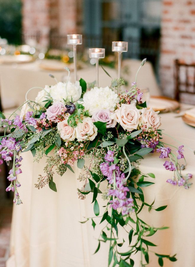 Historically speaking , purple and gold are the colors of royalty, and this Florida affairis pretty enough to be a royal wedding. From the anemone-accented bouquets to the soft gold table linens at the reception, every detail of this day exudes