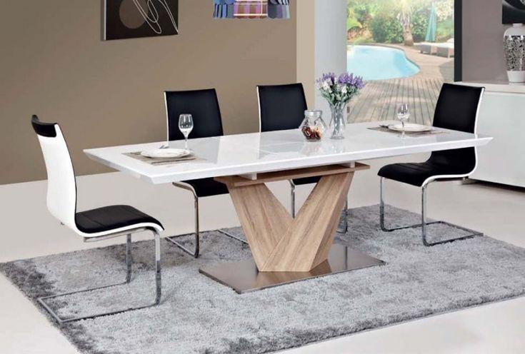 table à manger extensible à pied central en bois et métal, entourée de chaises en noir et blanc et un tapis gris clair