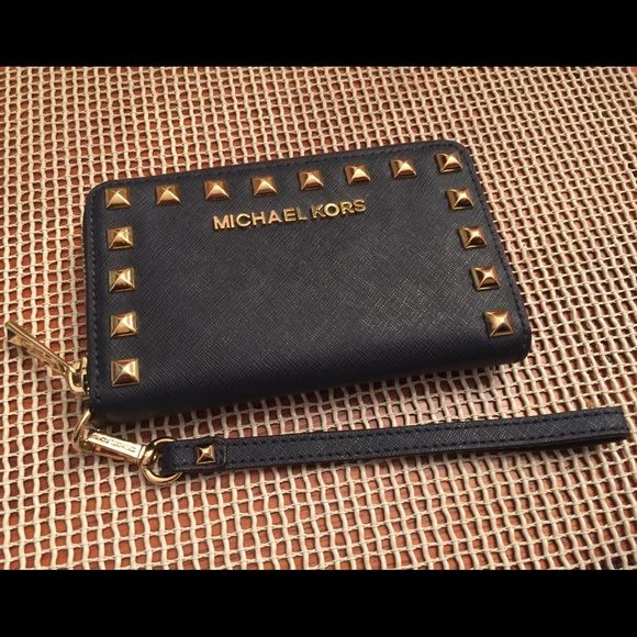 """🎉3 HR SALE🎉Micheal Kors Selma Wristlet 🎀Saffiano leather. Goldtone hardware. Zip-around closure. Pyramid goldtone studs. Center slip pocket for phone inside. 6(L) x 3.5(W) x 1(D)"""".6(L) x 3.5(W) x 1(D)"""" Tailored for the Apple iPhone® 5/5S and Apple iPhone® 4/4S models. BRAND NEW -NEVER USED. received it as a gift but I have the iPhone 6 Plus . Only reason for selling . New without tags . 🚫NO TRADES🚫 does not fit iphone 6 or 6 plus Michael Kors Bags Clutches & Wristlets"""
