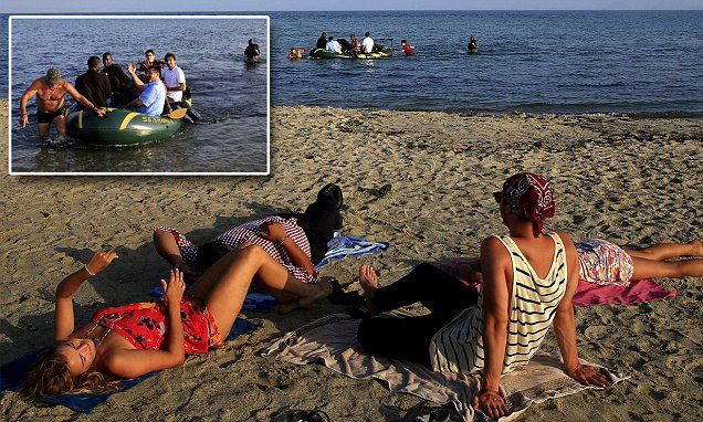 Sunbathers watch as rubber dinghy full of migrants arrive in Greece #DailyMail