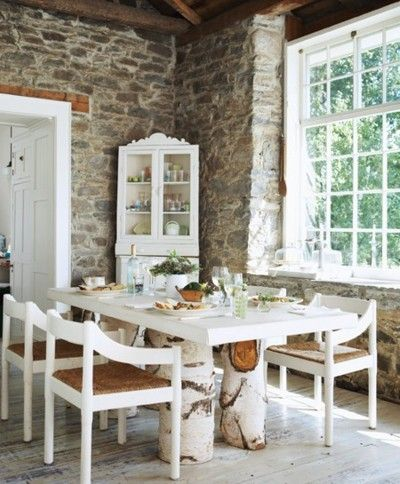 Rustic looking stone walls, tree trunk table legs and fabulous window