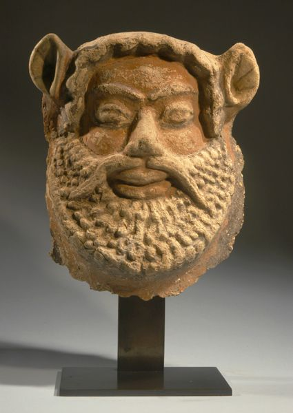 Etruscan polychrome terracotta satyr mask, 6th century B.C. Executed in the bold relief of the Archaic style, with a row of brow curls, pointed ears, broad moustache, thick lips, and a wide, curly spade-form beard; extensive polychromy remaining, 23 cm high Private collection