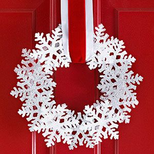 For an easy wreath in a flash, use premade snowflake ornaments (fiberglass or resin ornaments look especially frosty) and a flat foam wreath. Remove the string hangers from the ornaments and position on the wreath. Once you're satisfied with the arrangement, hot-glue the snowflakes into place. Thread wide ribbon (we layered red on top of white here) through the wreath and hang.