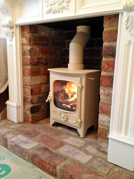 Charnwood Country 4 in almond with brick recess, timber surround and brick hearth.