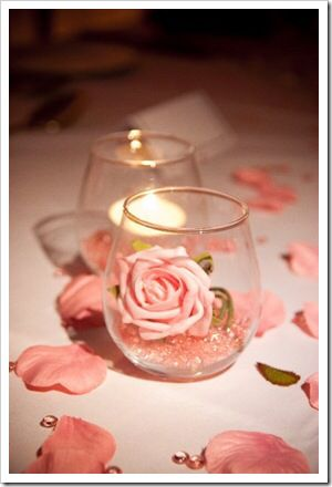 Easy centerpieces with stemless wine glasses, glitter or beads and a rose!