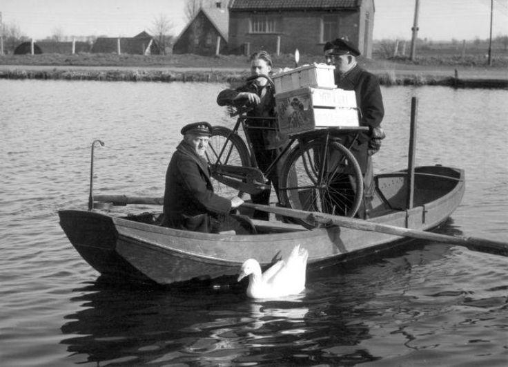 Een veerman zet met zijn roeiboot een aantal mensen over de vaart bij Lisse, 26 februari 1952. (Spaarnestad Photo)