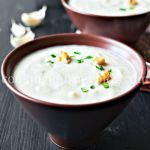 Cauliflower soup is smooth, silky, and absolutely tasty! This cauliflower soup recipe is healthy, gluten-free and vegan-friendly. So if you are looking into healthy cauliflower soup or mushroom soup combined together, they will deliver flavorful, creamy dish to serve. Cauliflower soup served in brown plates with walnuts and spinach on a black table.