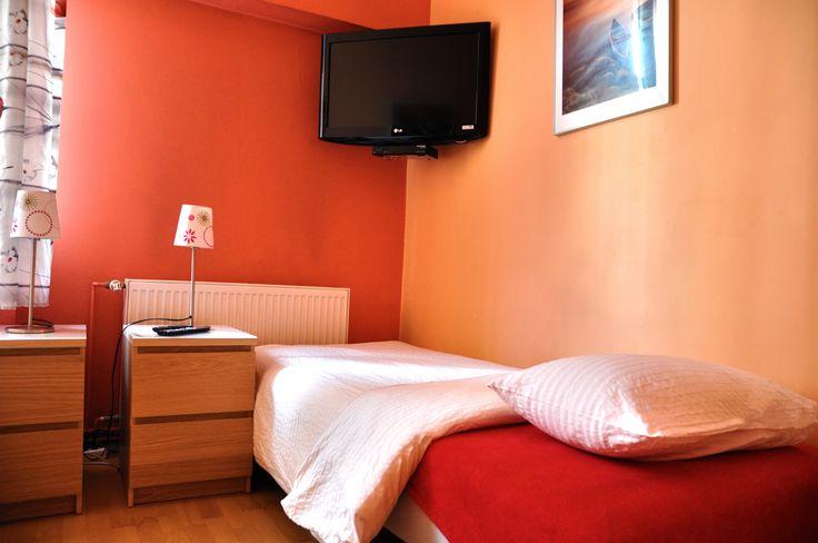 Sypialnia wyposazona w telewizor i nakasliki oraz lampki nocne  http://www.rainbowapartments.pl/pokoj-czerwony/