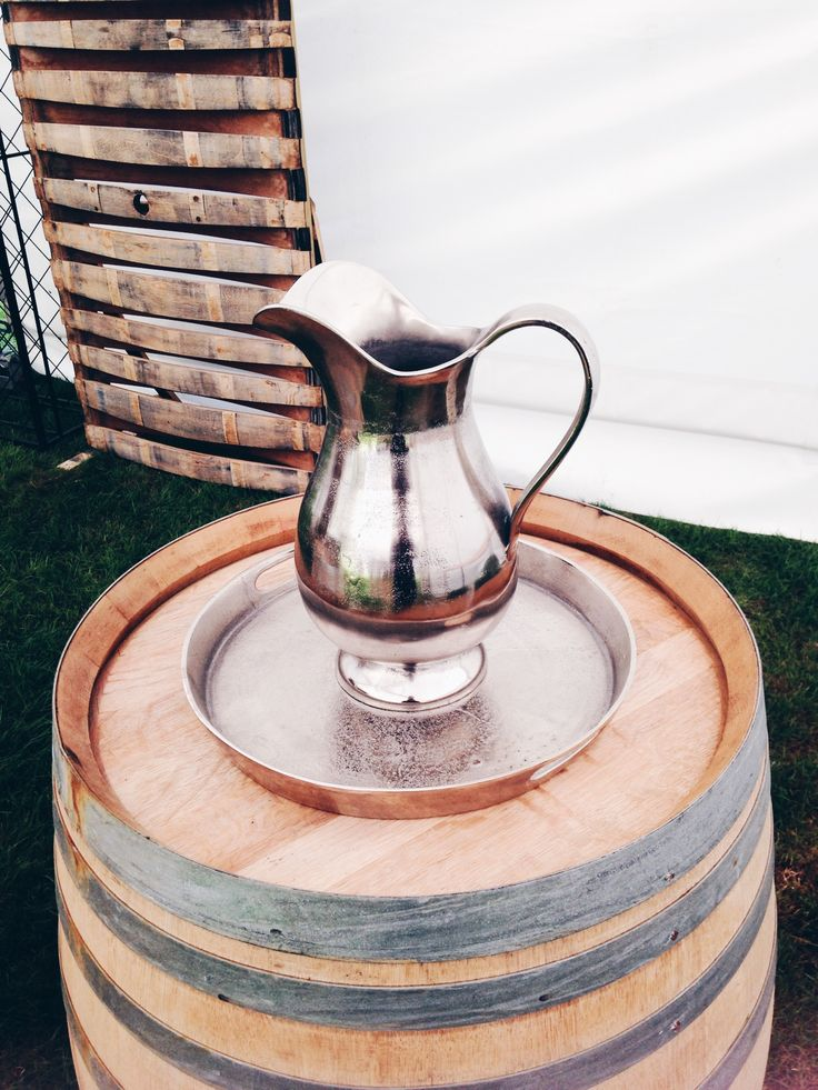 Sitting on a barrel the gorgeous vintage water pitcher that will add elegance to your event. Visit our website for more information