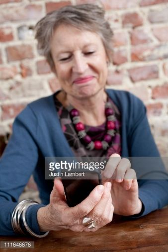 Stock Photo : OLDER LADY SMILING WHILE USING MODERN MOBILE PHONE