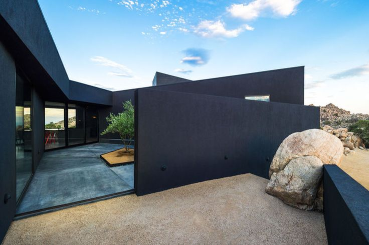 An unadorned black façade echoes the homeowners' brief but compelling instructions to the architects to design a house like a shadow.