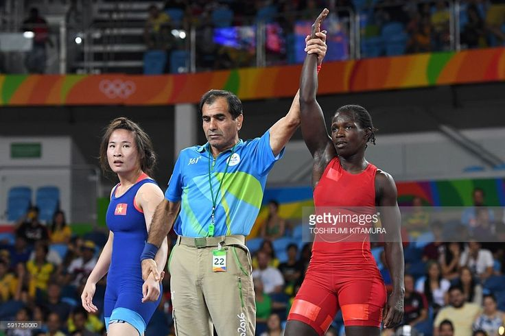 Senegal's Isabelle Sambou (red) celebrates winning against Vietnam's Thi Lua Nguyen (blue) in their women's 53kg qualifying match on August 18, 2016, during the wrestling event of the Rio 2016 Olympic Games at the Carioca Arena 2 in Rio de Janeiro. / AFP / Toshifumi KITAMURA