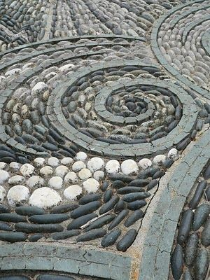 Perfect spiral concrete borders guide the pebble mosaic design