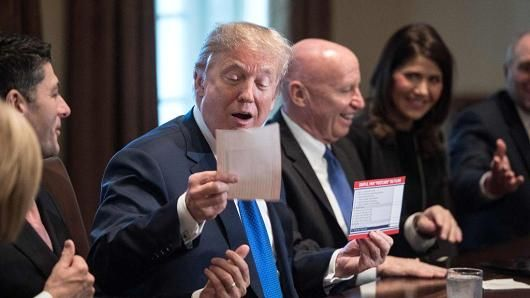 Over 400 American millionaires and billionaires plan to send a letter to Congress this week asking lawmakers not to cut their taxes.  11-12-17 US President Donald Trump looks at a sample of the proposed new tax form at the White House in Washington, DC, on Nov. 2, 2017.