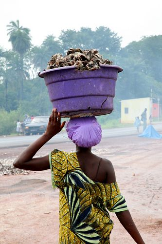 Africa |  Guinea-Bissau.   Woman carrying a bucket full of fresh oysters