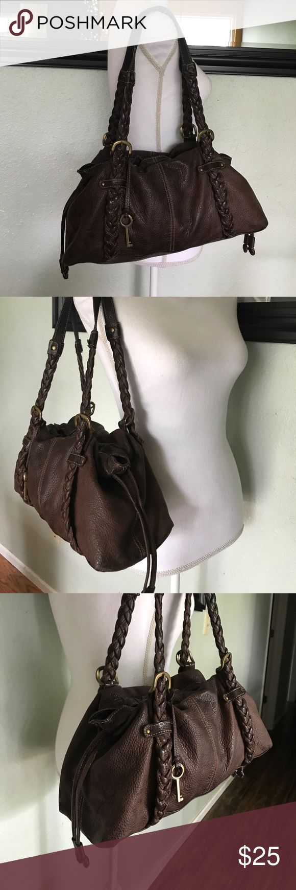 Fossil bag Beautiful brown fossil bag. Brown leather with two shoulder straps. Straps are a pretty braided leather. Top has a magnetic closure plus pull strings. Gold hardware. There are some marks that may come out with leather conditioning. No rips or holes though. Inside has one zipper pocket and two pouches. Height 9, width 15 1/4, depth 5, handle drop 10. Fossil Bags