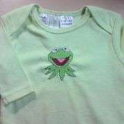 $14.95      Kermie!   Size 0000  Kermit the Frog, Size pale green long sleeve bodysuit  One for the parents I think!! There just aren't enough Muppets in the world anymore.  Lovely soft T-shirt fabric, quite thick and warm.  Low Fire Danger Cotton  Sized to fit Height 56cm  Weight 3kg