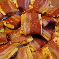 Bacon Crackers   Our Pianist made these for a social tonight at Church and YUMMMMM!!! Hope you get the chance to try this recipe...there are only 3 ingredients.  Club Crackers  1/2 Slices of Thin Bacon  Parmesan Cheese    Bake it at 200 Degrees for 1 1/2 - 2 hours. You wont believe how great they are!!!