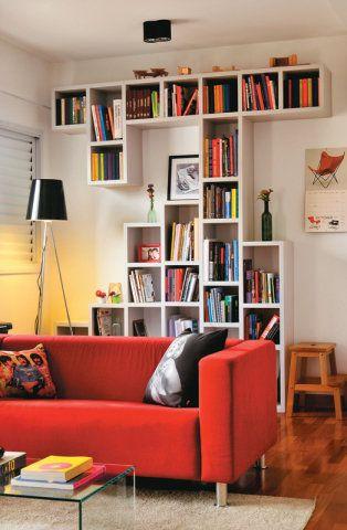 """A estante vale por uma escultura. """"Partimos do Modulor, sistema de proporções criado pelo arquiteto Le Corbusier"""", fala Renata. Assim, ela e Thiago projetaram o móvel com medidas práticas e harmoniosas, que aproveitam bem o espaço. Sofá de sarja. Modelo Neo (1,68 x 0,85 x 0,65 m). Etna, R$ 799,90. Estante de MDF. Marcenaria Esdras, R$ 2 150. Luminária Com cúpula de vidro preto (1,70 m de altura). Yamamura, R$ 290 (em promoção)."""