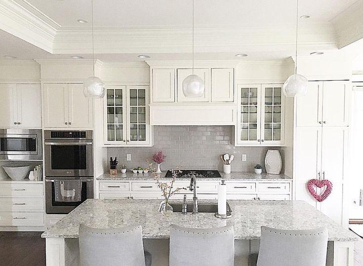 White kitchen with grey subway tile backsplash and shaker cabinets. Benjamin Moore White Dove. Glass front cabinets. LG Viatera quartz countertops. @carolineondesign