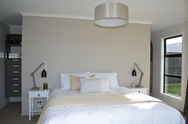 The master bedroom with storage behind the bed. While the walls and ceiling employ the same colour scheme as the living spaces.