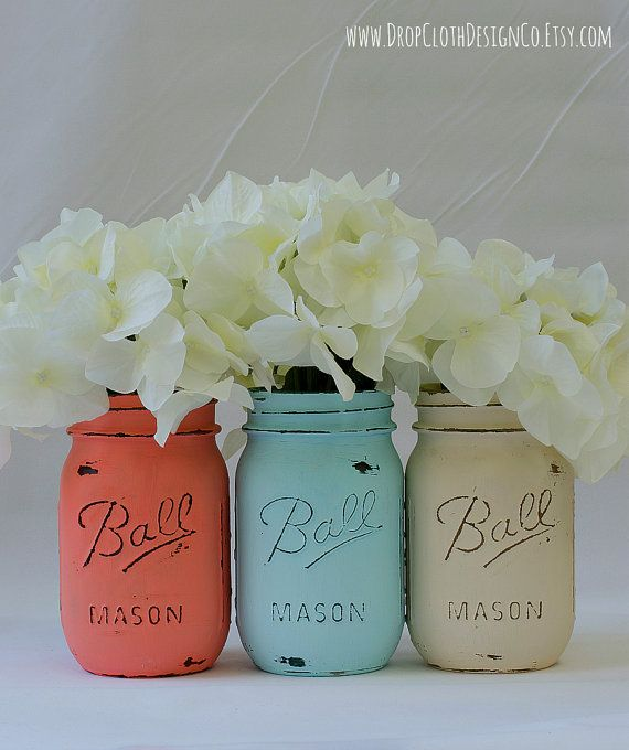 Set of 3 pint-sized mason jars painted and distressed in coral, blue, and cream colors. Perfect for weddings and showers, centerpieces,