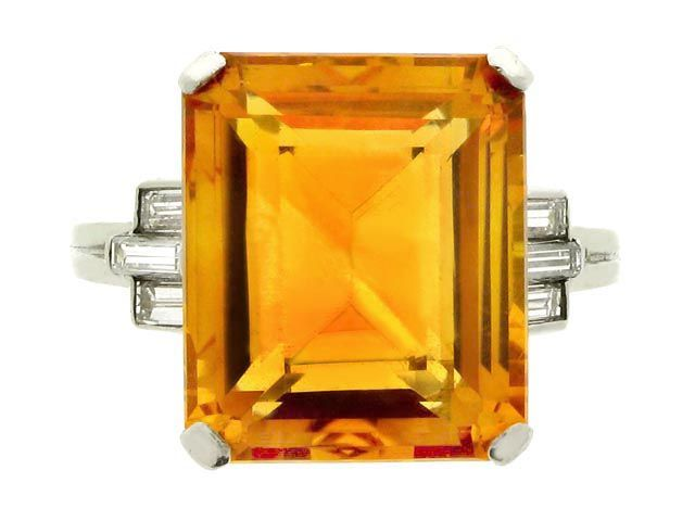 Art Deco citrine and diamond ring by Tiffany & Co, American, circa 1930. A platinum and iridium ring set with one central rectangular emerald-cut citrine in a claw setting with an approximate weight of 9.00 carats, flanked by raised shoulders set with six baguette cut diamonds in a stepped formations with an approximate total weight of 0.50 carats, and on a ribbed square shank.