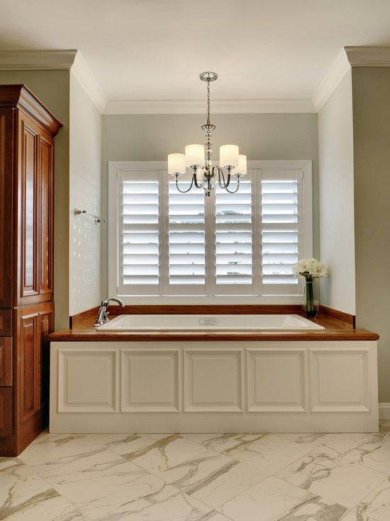 Understated Elegance In This Raised Panel Tub Surround, Plantation Shutters  And Polished Nickel Light Fixture