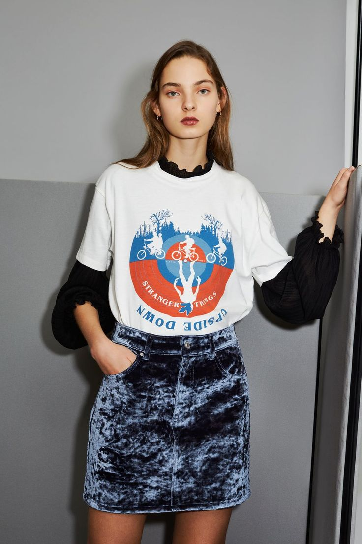 Merchandise gets a modern update with our Stranger Things collaboration. We're styling this ecru 'Upside Down' slogan and print t-shirt with a velvet skirt for total eighties nostalgia. Try wearing it over blouse or shirt for a retro-inspired look.