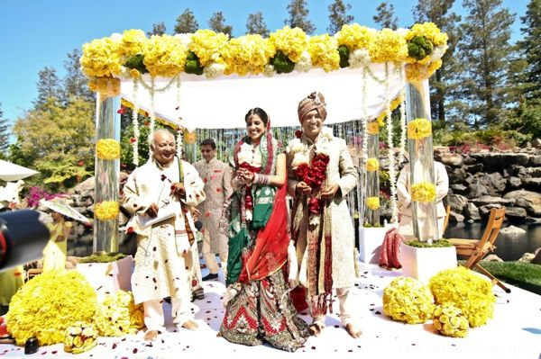 Indian wedding traditional ceremony outdoors. Colorful and bright mandap with a lot of flowers.