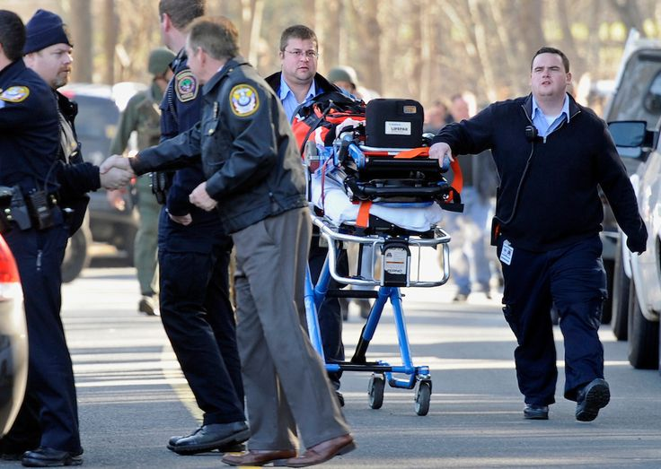 an empty gurney is pushed by medics away from sandy hook elementary school after a mass shooting that claimed the lives of 26 people including 20 children