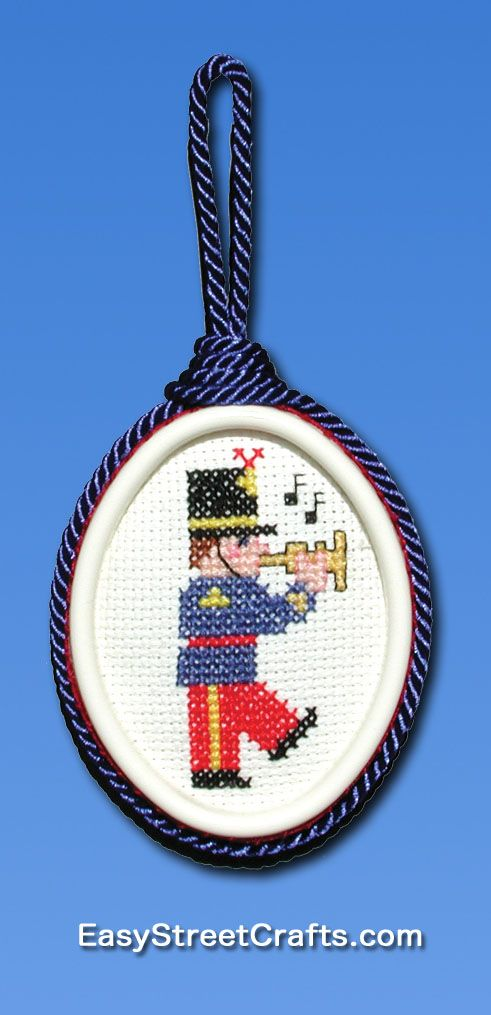 "MARCHING SOLDIER TOOTING HIS HORN AT CHRISTMAS TIME - - - stitched on 14-count Aida cloth and framed in Sweet Suspension oval frame, Chart is in booklet ""Stitch Christmas Ornaments All Year Round"" from EasyStreetCrafts.com"