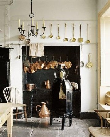 A Georgian Kitchen with copper pans hanging around a fireplace
