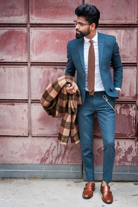 Ce look illustre bien le style italien par excellence : un costume très ajusté aux couleurs plus originales que la moyenne avec un bleu pastel texturé. L'ensemble est relevé par une cravate assortie aux chaussures à double boucles. Une chaîne vient se placer sur le côté du pantalon pour casser le côté formel. A noter que le manteau du mannequin est facilement portable dans cette tenue