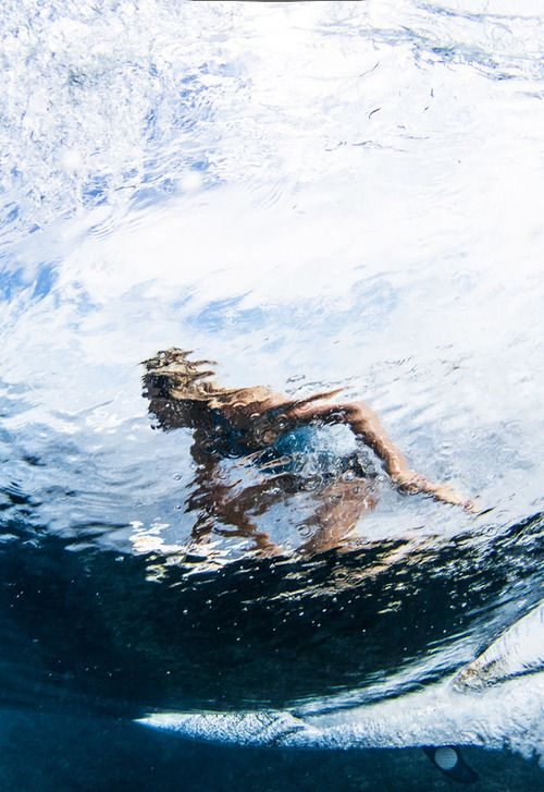 A woman surfing, seen reflected on the water.