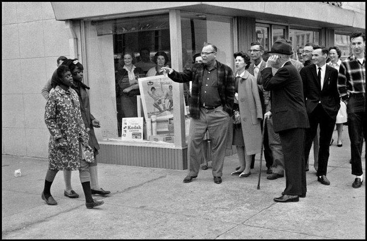 Hecklers insult two black women who are part of a voting rights drive in Selma Al, 1965.