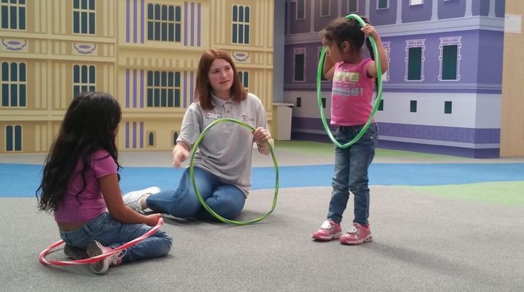 Staff member playing hula hoops with two girls at Under 1 Roof Kids