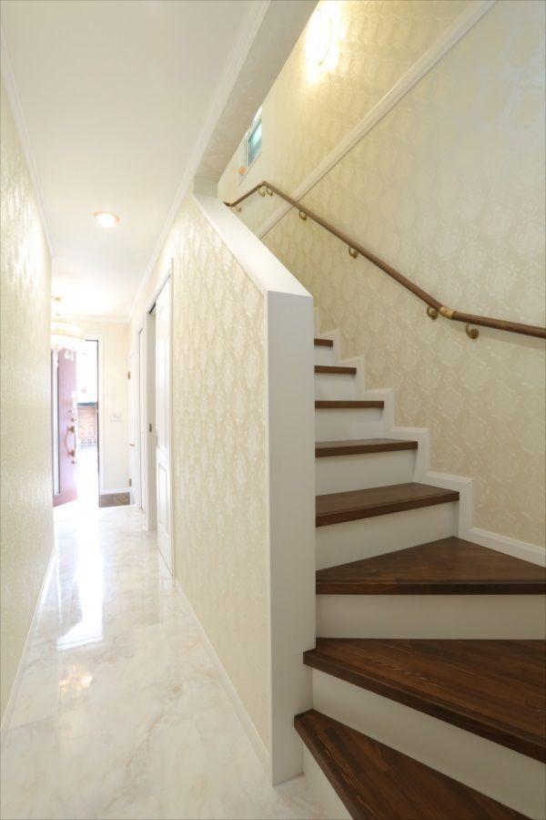 ダマスク柄の壁紙が印象的な階段ホール 茶色と白のコントラストが
