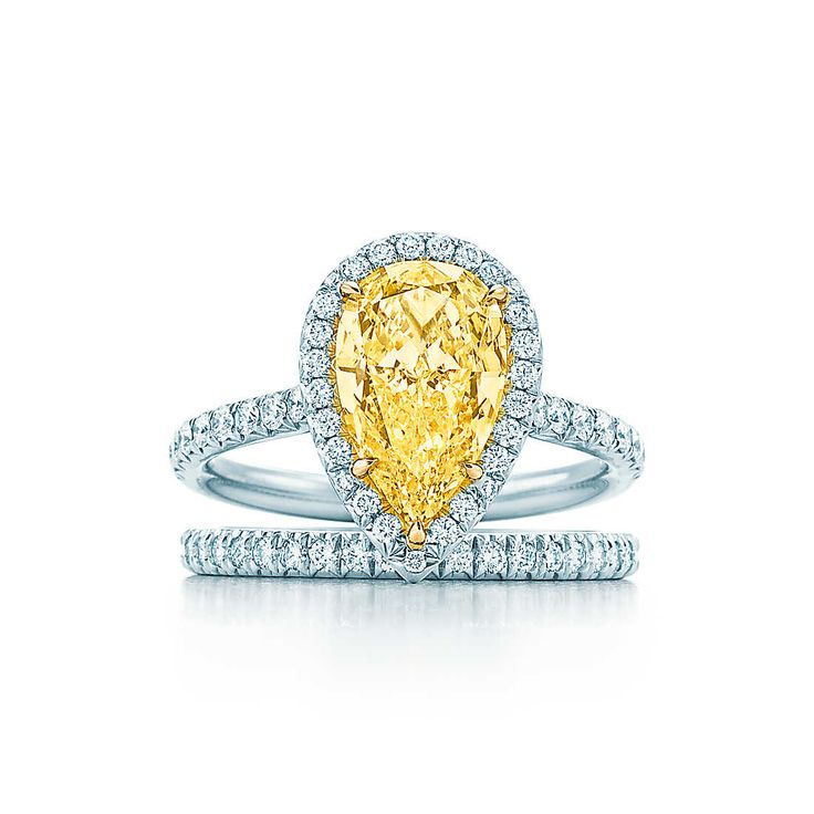 This ring is classically elegant with a pear-shaped yellow diamond encircled by a single row of bead-set white diamonds. A diamond band enhances the striking magnificence of this piece.