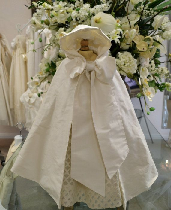 Stylish outerwear, perfect compliment to any special occasion dress or gown!  This hooded baby cape is made of silk shantung and is fully lined. Fastens with long sashes that tie into a precious bow, at the neckline two hand covered buttons.  Ideal over a flower girl dress, baptism/christening gown or dress, or Easter dress to keep the little one warm in a way that previews and enhances the dress or gown beneath.  Offered in 3-12 months, as shown in ivory. Also available in white…