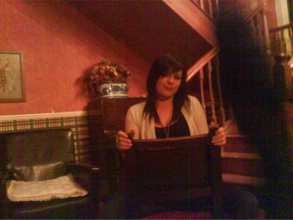 This photo of me was taken around 4 years ago by an ex boyfriend . It was in an old pub in Dumfries, Scotland. I never noticed until a few months ago the dark figure beside me. At the time the photo was taken it was only me & my ex in that certain part of the pub, absolutely no one else around. It spooked me looking at it. I have no idea what it is looming beside me. Submitted by: Donna W. Scotland