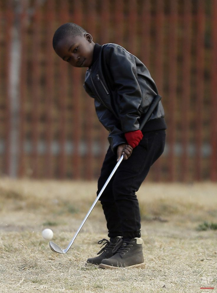 Six-year-old Ntando Gumede, chips the ball during a game of golf at a park in Katlehong township, east of Johannesburg, South Africa, Thursday, July 16, 2015. (AP Photo/Themba Hadebe)