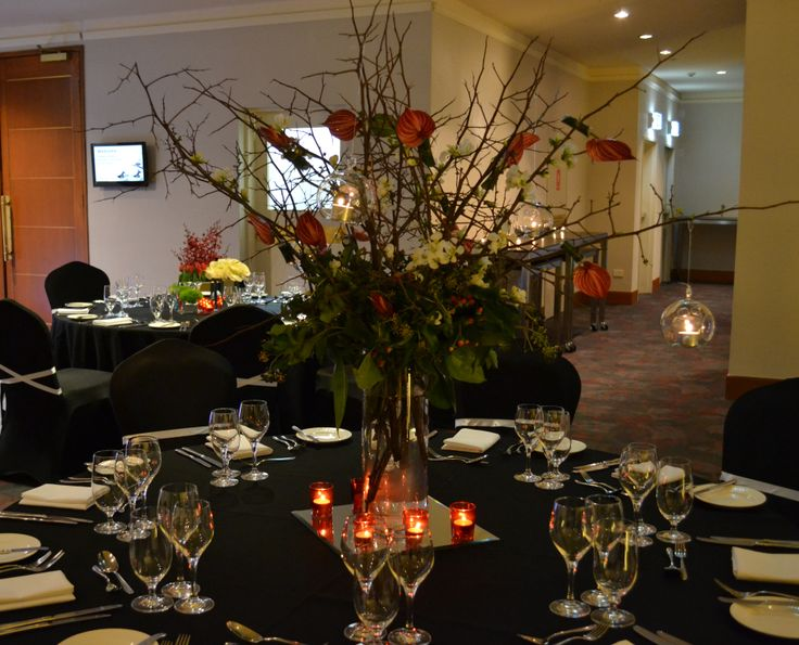 Tall branches with anthuriums and hanging votive glass balls. Styled by Greenstone Events.