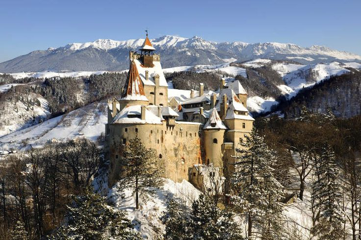 Snow-covered Bran Castle and Bucegi Mountains. Image by warmcolors / iStock / Getty Images
