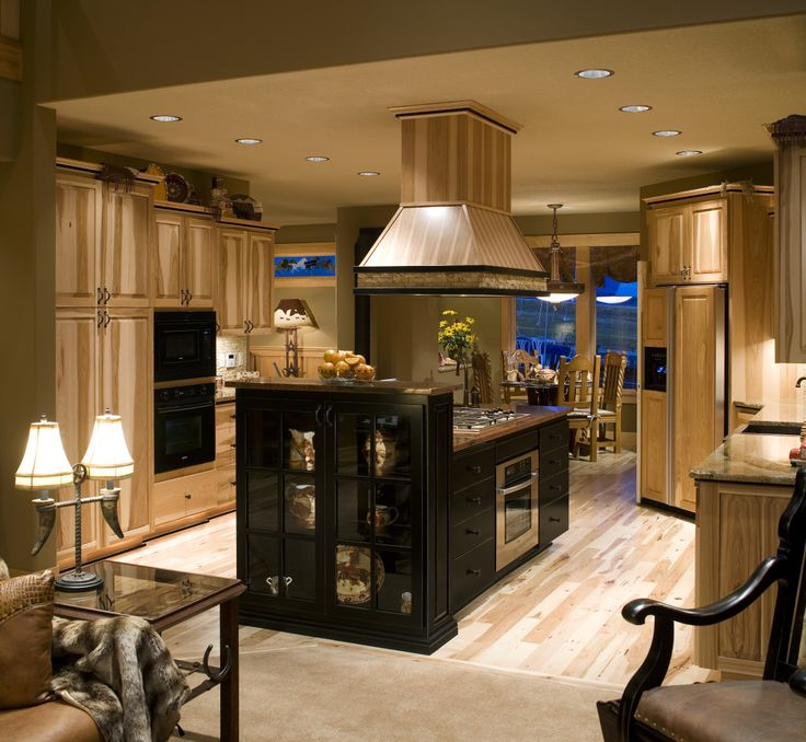 This rustic home completely redid their kitchen, adding cabinet crown molding, wood around their fridge and hood, hardwood floors and undercabinet lighting. The warm feeling you get as you enter the kitchen is due to a combo of wood and ambient lighting.