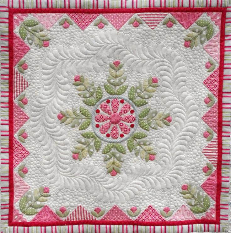 "Snowflake Medallion quilt, center, by Christabel.  The design is by Emma and Pam Jansen.  Custom quilting and photography by Quilts on Bastings (Australia).  She says: ""I have surrounded the centre applique design with a wreath of feathers and filled with my favourite background fill - pebbles."""