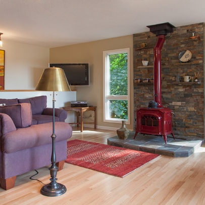 Another view of the red woodstove and slate fireplace surround in the cheerful family room, showing the furniture placement and more of the red rug that looks so good with the woodstove. Large flatscreen TV in corner does not detract from main focal point in room (the woodstove, hearth and slate fireplace surround with rock shelves displaying pottery), nor the views from the lovely windows flanking the woodstove.